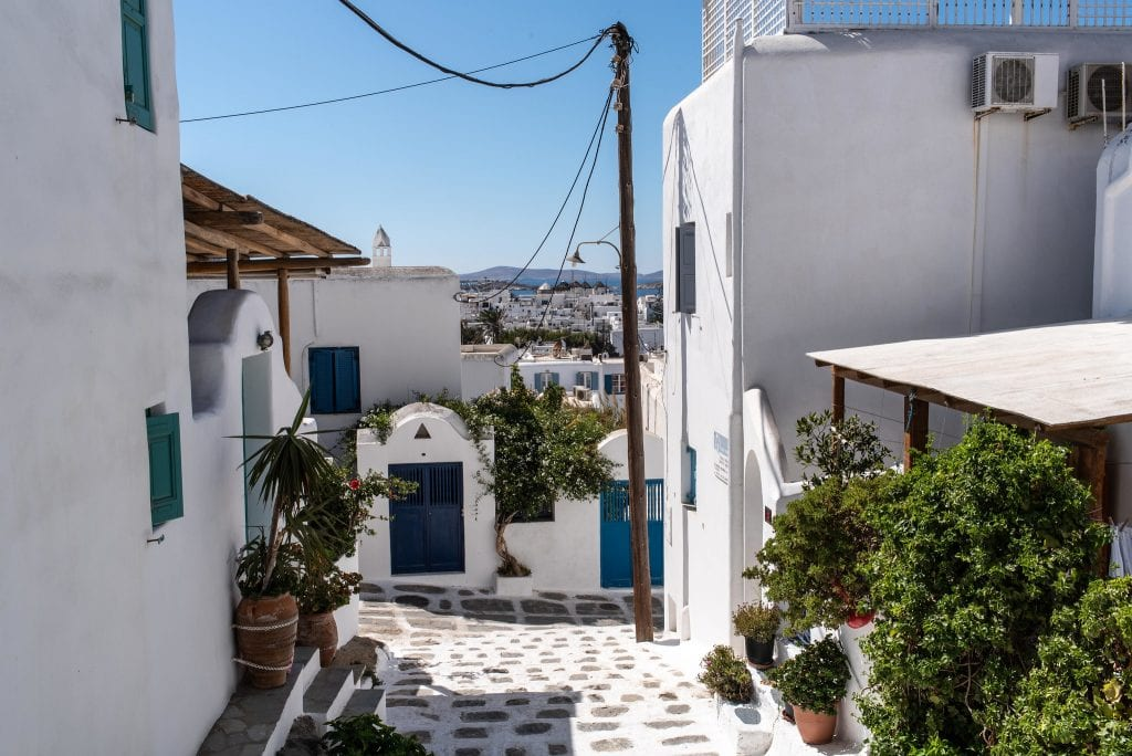 Mykonos alleyway with white houses and plants