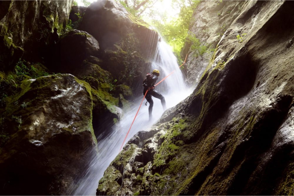 Man rappelling near waterfalls